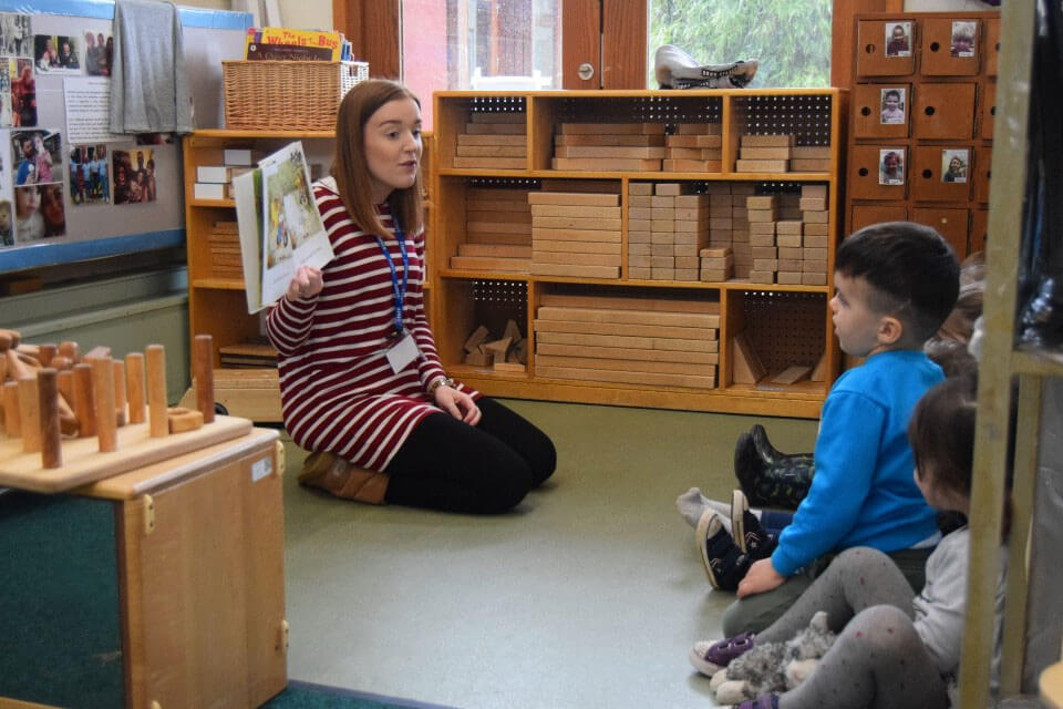Practitioner reading to a group of children